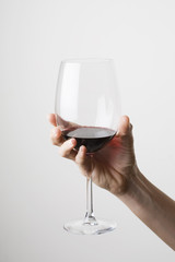 Hand holding a glass of red wine