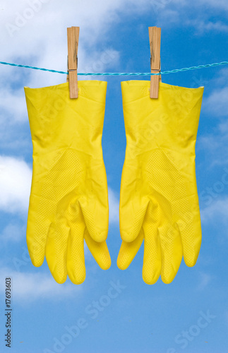 yellow gloves drying on rope