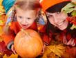 Happy family with child on autumn orange leaf, pumpkin.