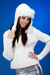 Portrait of winter girl wearing white hat. blue background