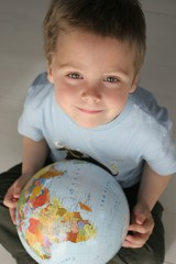child, small boy holding a colourfull ball-a globe