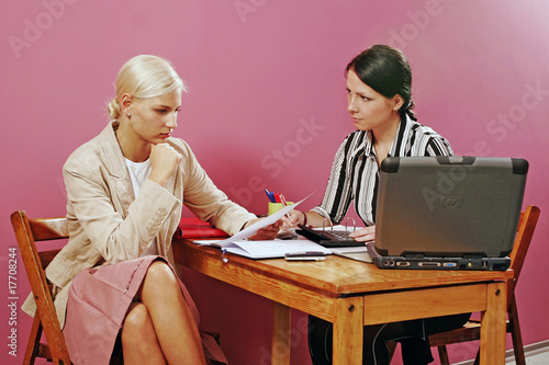 two young women discuss on pink