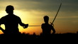 :  Men at sunset fighting with swords