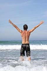 Young energetic man enjoying freedom standing in the ocean