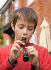 young boy playing a recorder outside