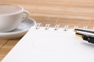 pen, notebook and cup of coffee