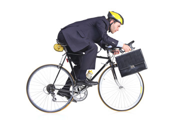 Businessman in a suit with a briefcase riding a bicycle