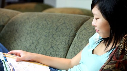 A pretty  Asian girl on a couch studying from a textbook.
