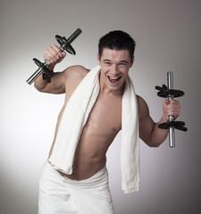 homme serviette levant haltères sourire