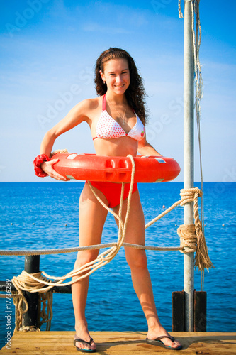 Girl with life saving buoy on pier