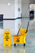Mop and Bucket with Caution Sign