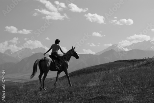 Girl riding a horse in the mountains