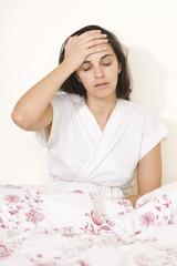 Junge hübsche Frau mit Kopfschmerzen im Bett