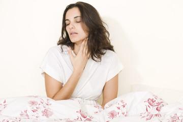 Junge hübsche Frau mit Halsschmerzen im Bett