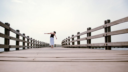 Girl balances on pier