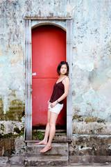 Girl leans in red doorway