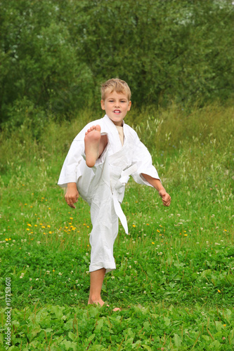 Karate boy kick a leg outdoor