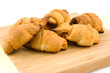 wooden board with home made croissants over white background