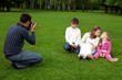 man photographes his family outdoors
