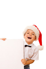 Laughing christmas boy with santa hat and blank sign