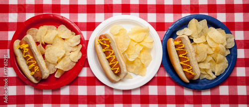 Several hotdogs on colored plates