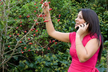 Girl in garden analyzing fruit while talking on cell phone