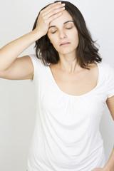 Junge hübsche Frau mit Kopfschmerzen