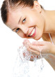 Happy beautiful woman wash her face