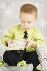 cute litle boy opening xmas gifts