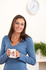 Happy young woman holding cup of coffee