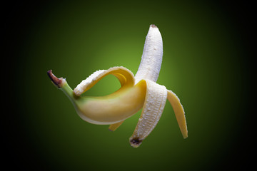 Floating peeled fresh banana on greenish background