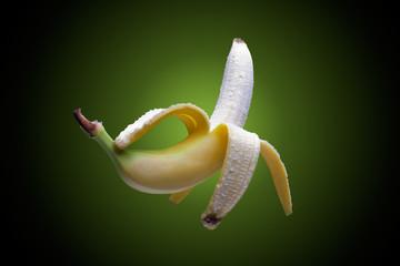 Floating peeled fresh banana on greenish background