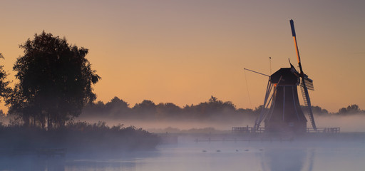Typical windmill from the Netherlands at sunrise in the fog