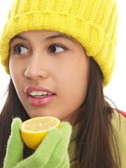 girl in winter cap holding a fresh lemon