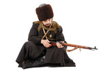 Russian Cossack inspecting a rifle in siitting position.