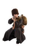 Russian Cossack points a rifle at camera in squatting position.