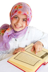 Little girl reads Koran and smiles
