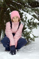 Girl in pink winter clothing on the snow
