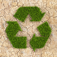 Recycle symbol made with grass on dry cracked earth