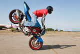 Stunt rider making stoppie poster