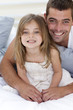 Portrait of smiling father and daughter in bed