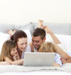 Parents and children in bed playing with a laptop