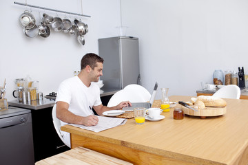 Man working in kitchen while having breakfast