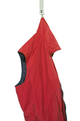 Abstract: a red sleeveless jacket hanging on a snap-hook