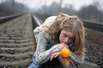 lady with orange on railways
