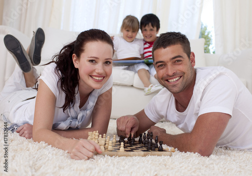 Happy couple playing chess on floor in living-room