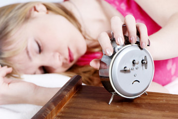 Young beautiful girl switching off alarm clock