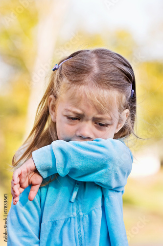 Young child coughing or sneezing into her elbow.