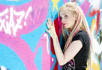 portrait of young woman standing at graffitti wall