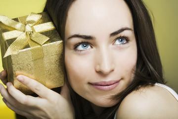 neugierige junge frau mit geschenk in der hand